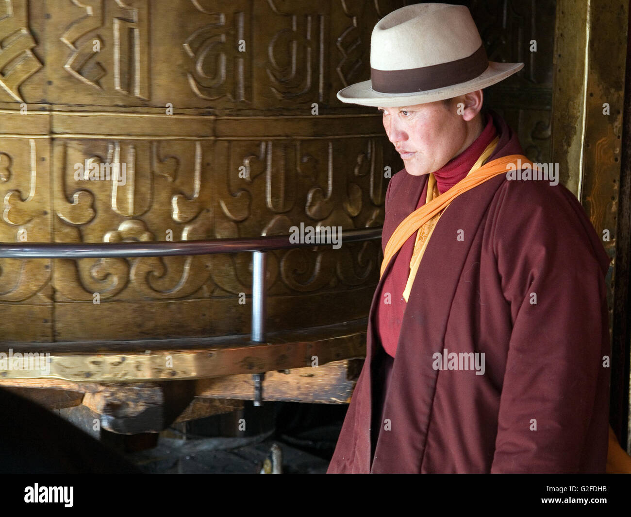 Pilgrim rotates prayer wheel in  Jokhang Temple. - Stock Image