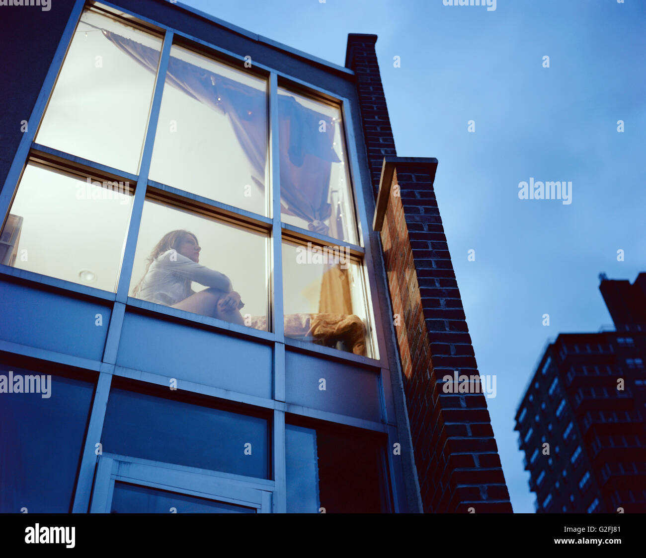 View from Outside of Young Adult Woman Gazing out Window at Night, Low Angle View - Stock Image