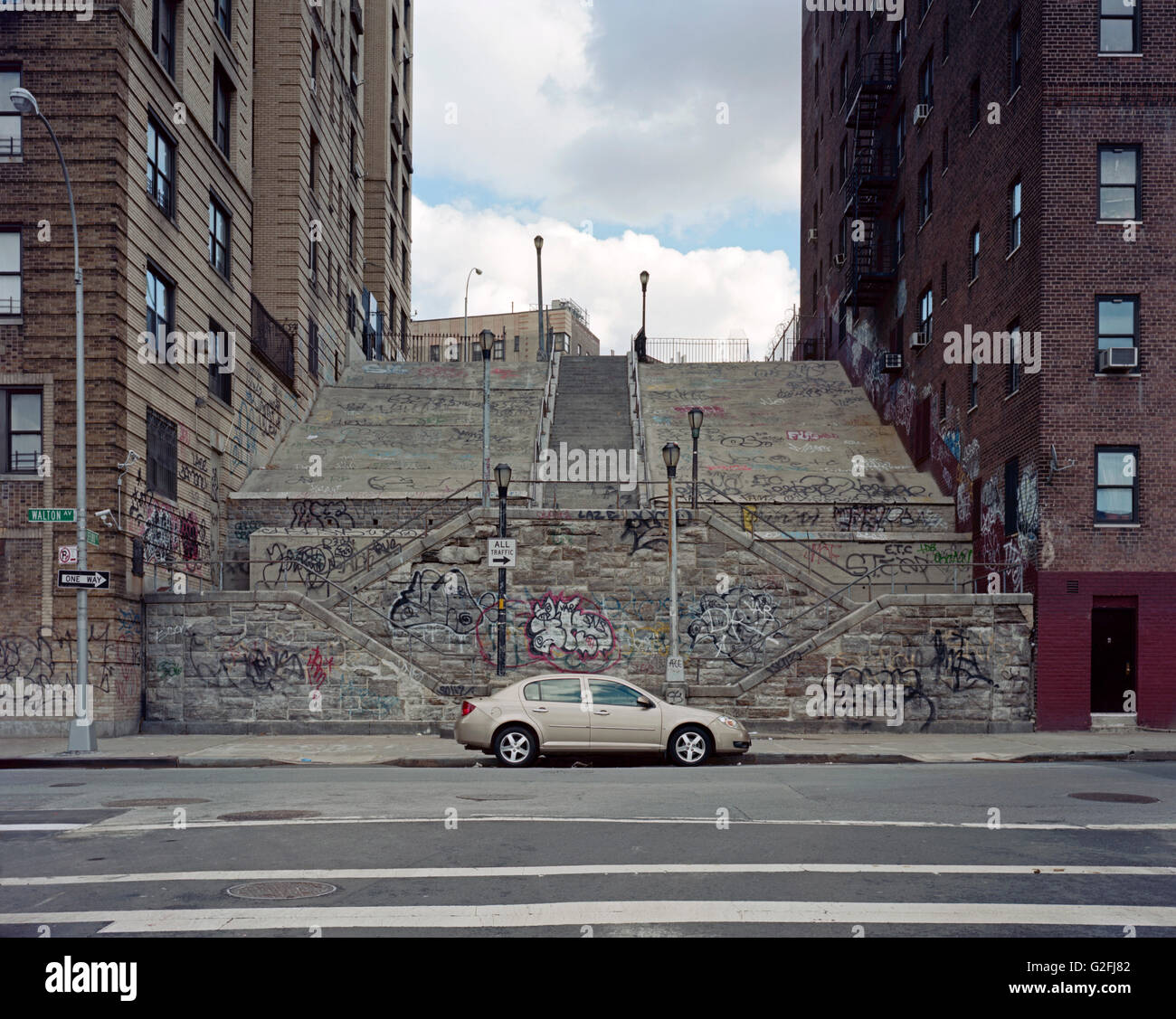 Parked Car at Base of Large Stairs Between Two Buildings, Graffiti, Bronx, New York City, USA - Stock Image