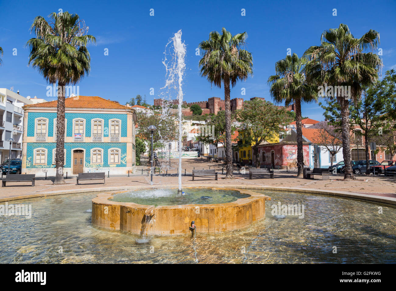 Fountain in public space with castle on skyline, Silves, Algarve, Portugal - Stock Image