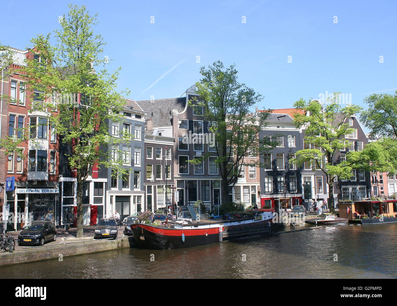 Old warehouses and house boats moored along Prinsengracht canal, Amsterdam, the Netherlands. (opposite Anne Frank - Stock Image