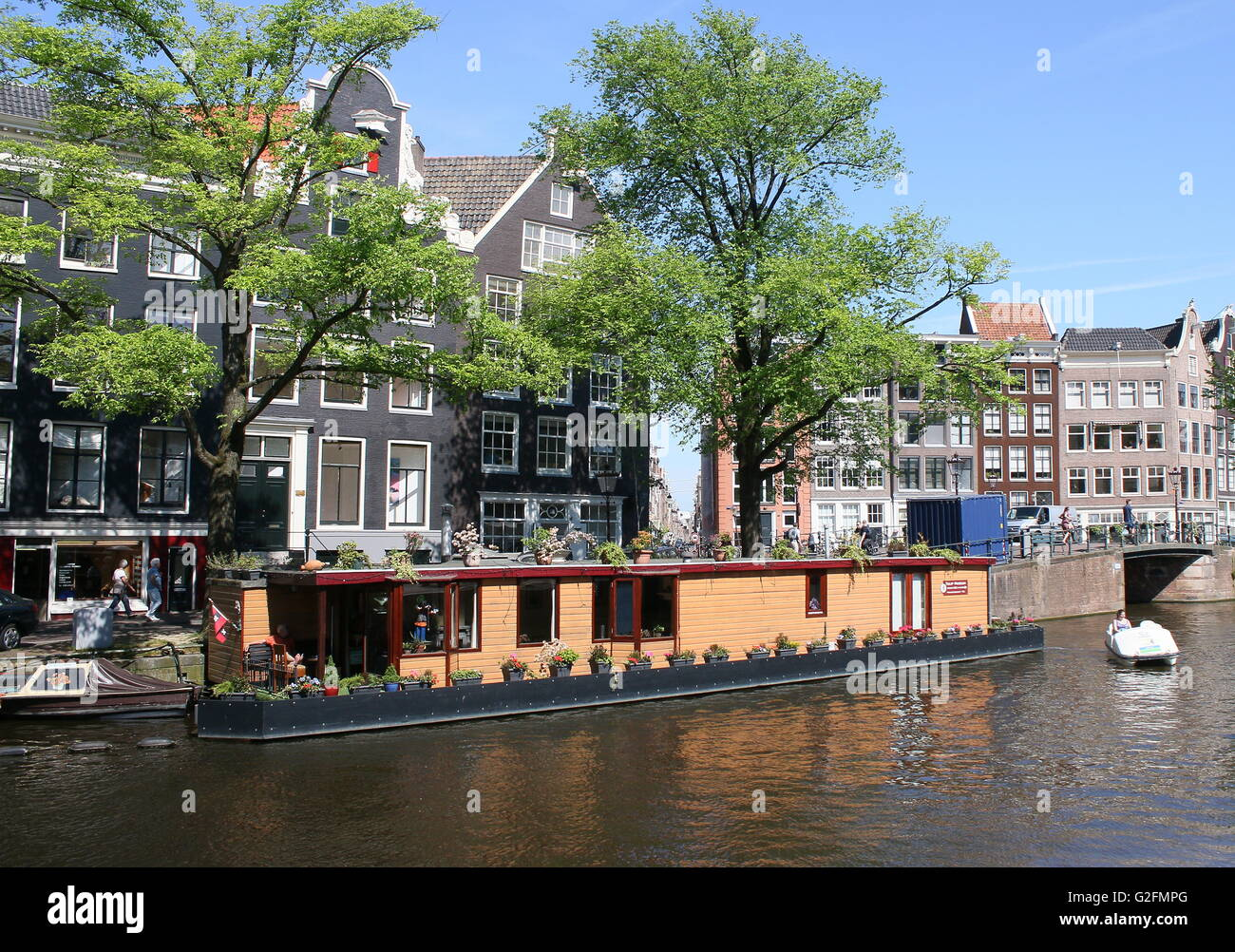 Typical Dutch wooden house boat moored along Prinsengracht canal, Amsterdam, the Netherlands. (opposite Anne Frank - Stock Image