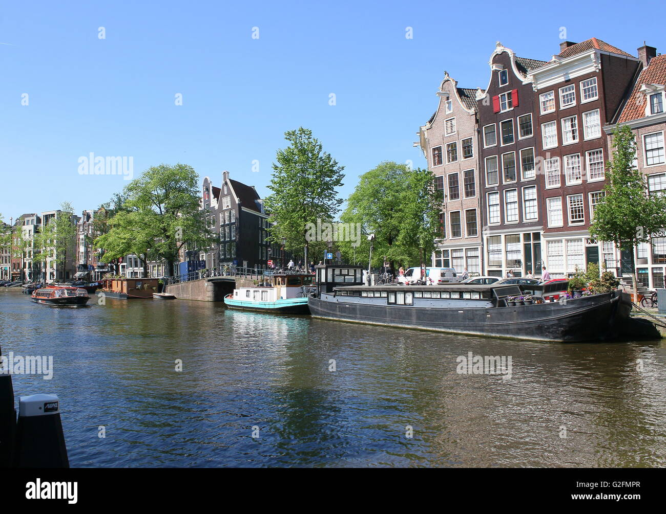 17th and 18th century warehouses and house boats moored along Prinsengracht canal, Amsterdam, the Netherlands. Spring - Stock Image