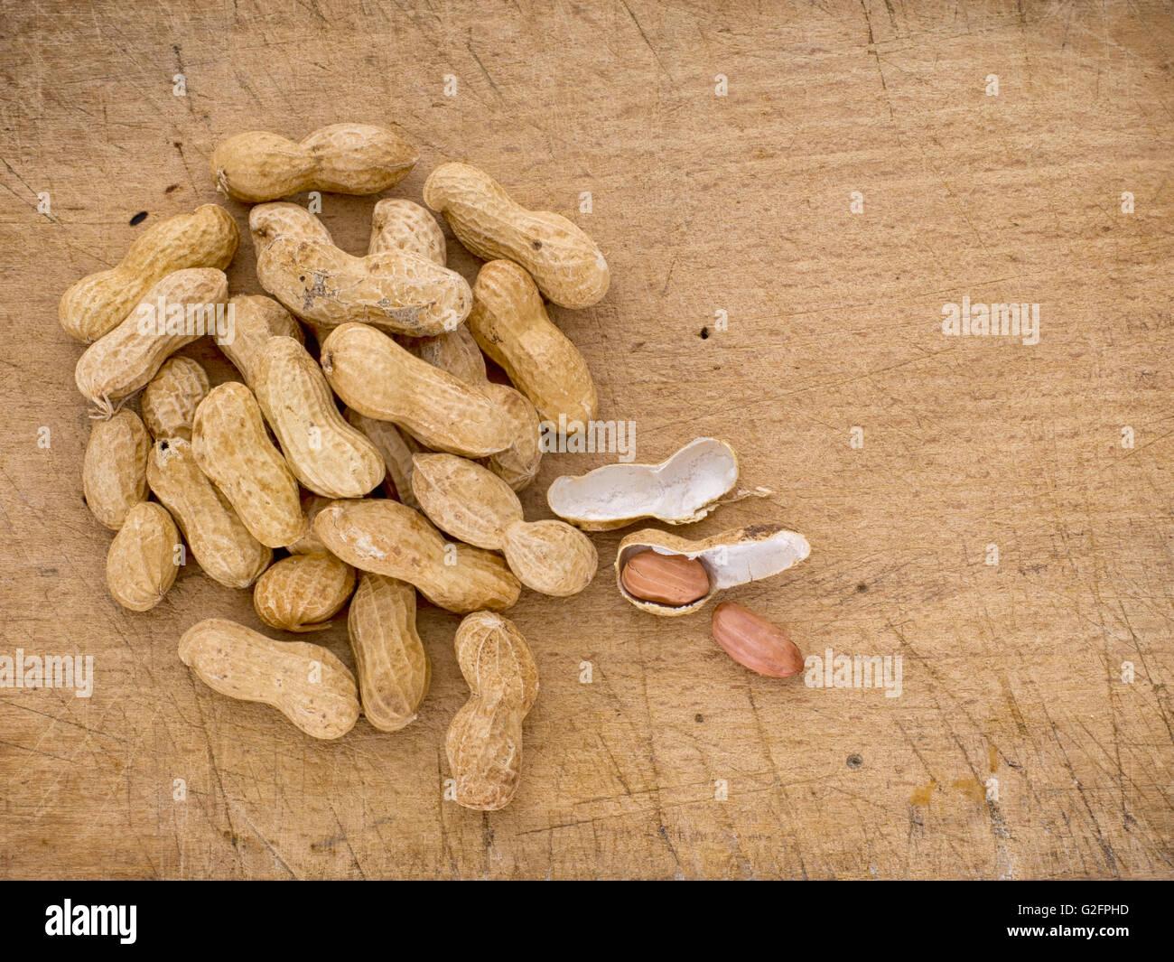 Monkey nuts aka peanuts aka groundnuts on board in shells. Stock Photo