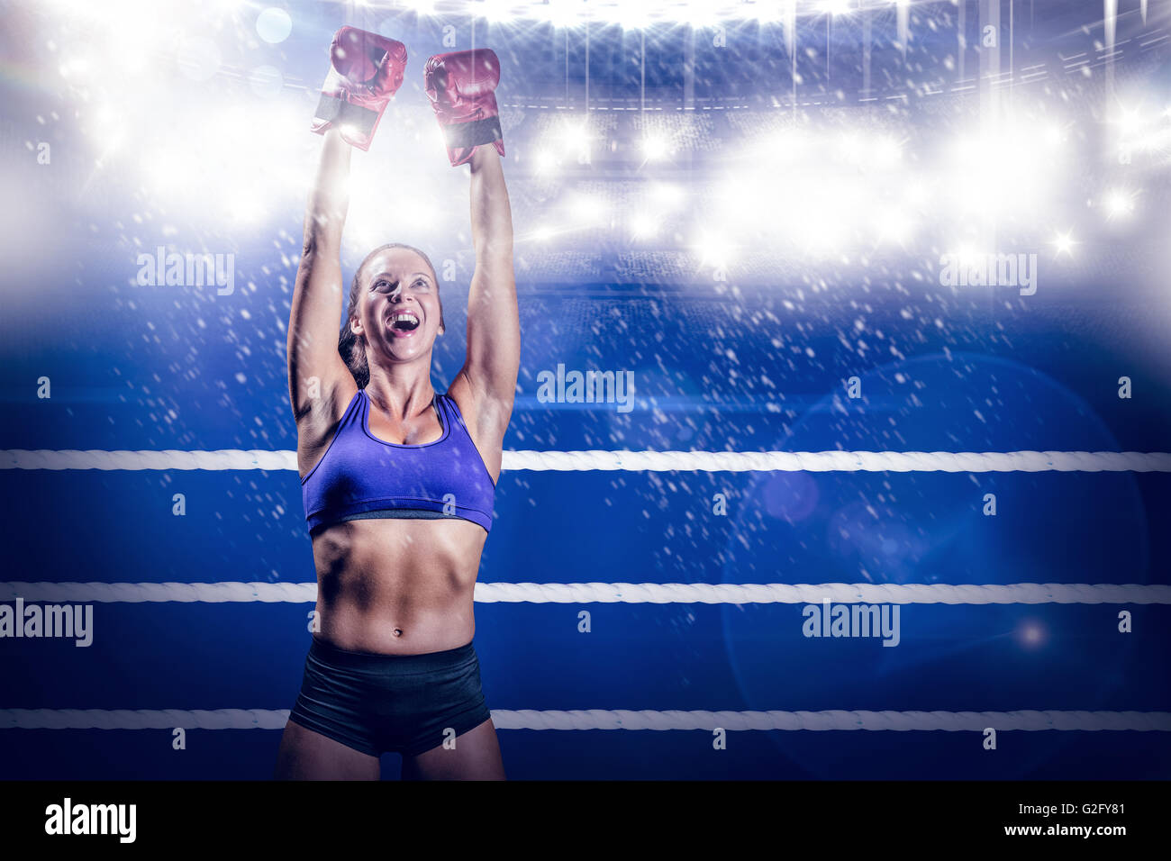 Composite image of winning fighter with arms raised - Stock Image