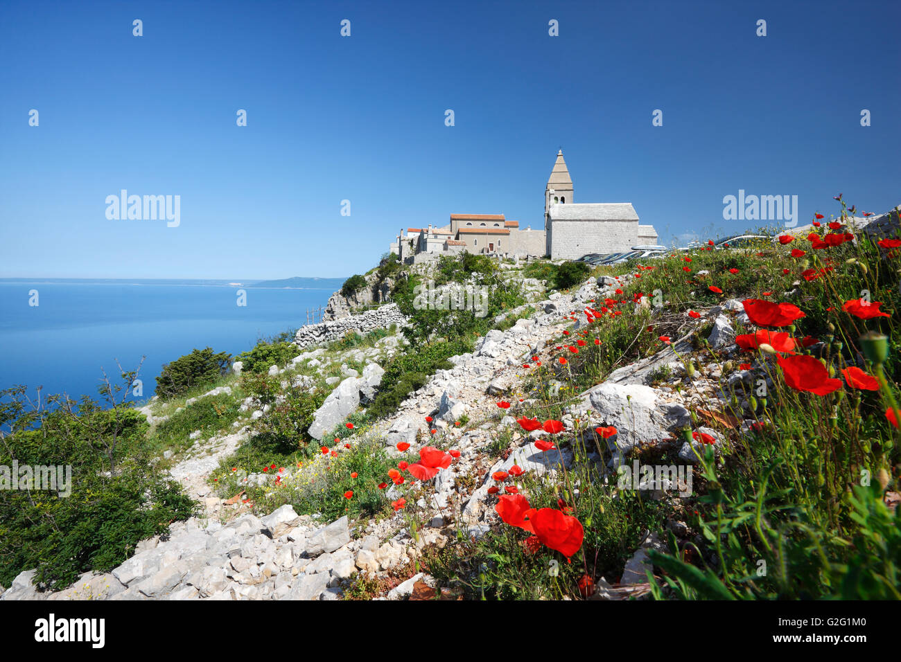 The hilly Lubenice town on the Island of Cres with poppy flowers in the front - Stock Image