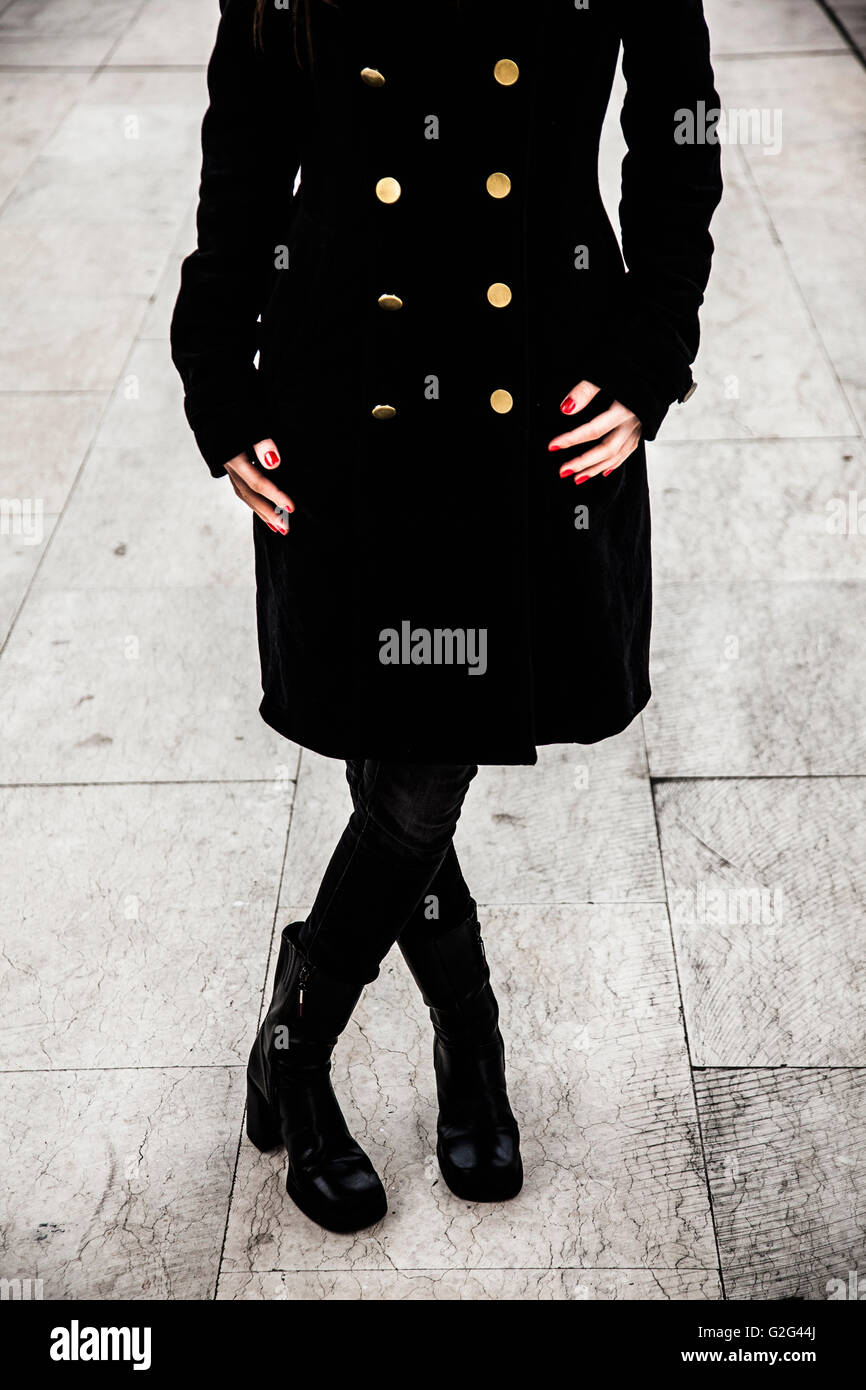 Woman Wearing Black Coat with Gold Buttons and Black Boots, Close-Up View From Torso-Down - Stock Image