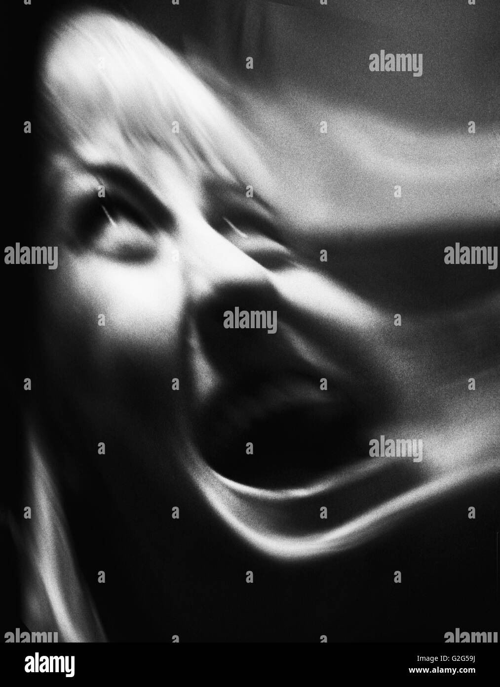Distorted Portrait of Woman Screaming, Close-Up - Stock Image
