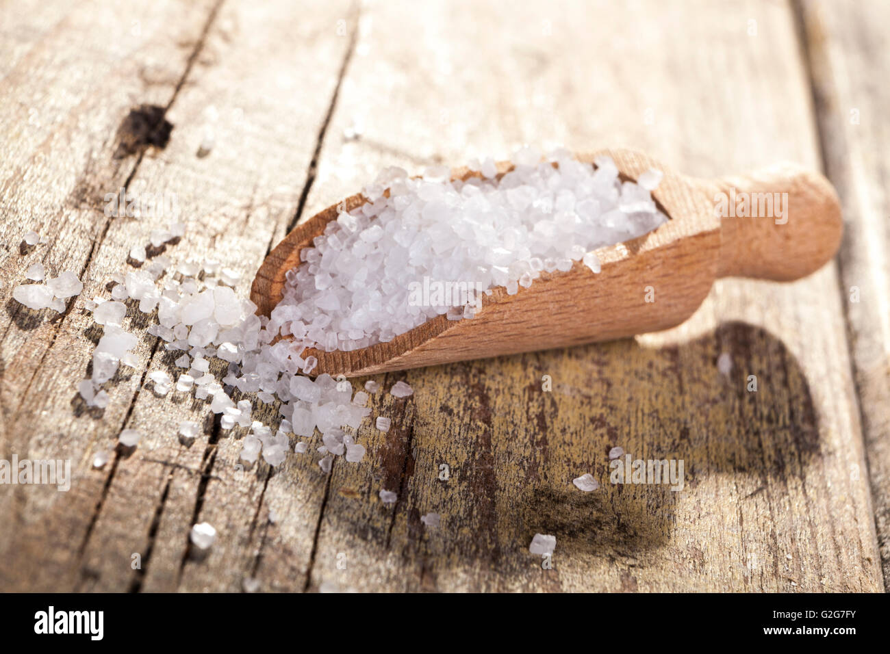 Old Brown wood spoon with salt cristals on wood table - Stock Image