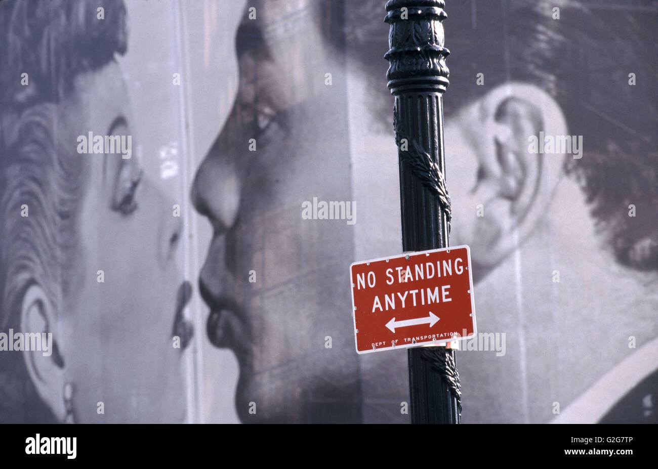 A 'No Standing' parking sign rises in front of a billboard in New York City. - Stock Image