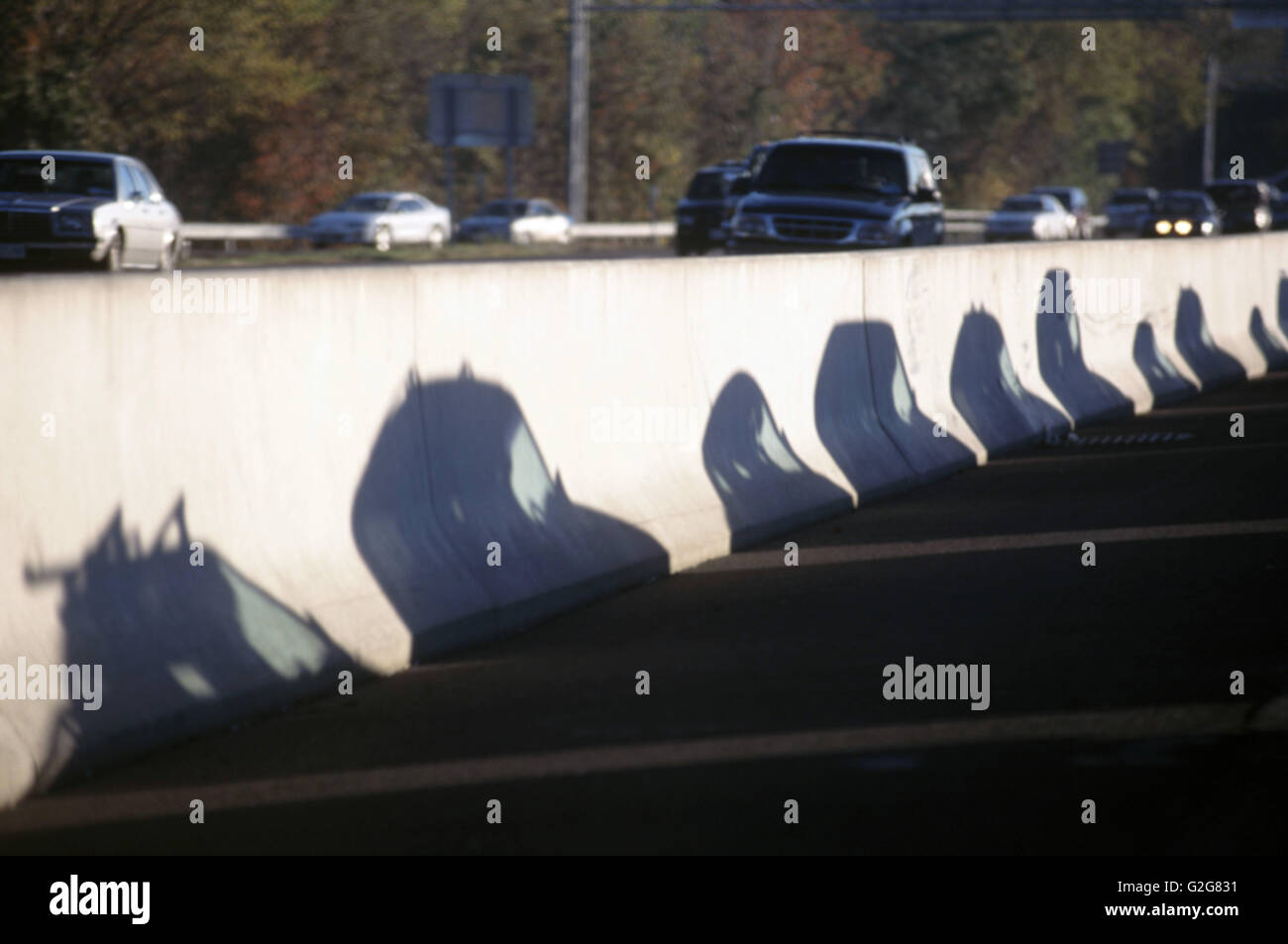 Highway Traffic. Cars shadows appear on concrete median barrier - Stock Image