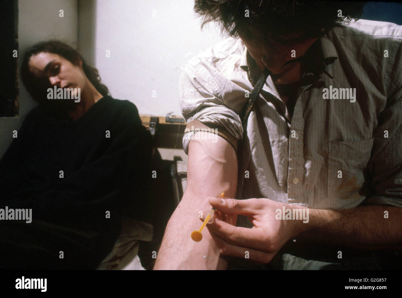 A heroin addict shooting up while his girliend is already high. - Stock Image