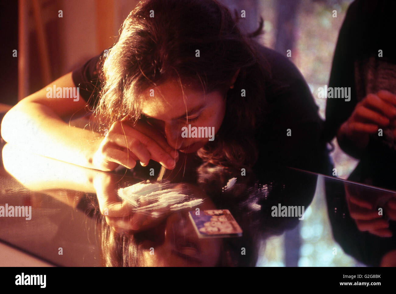 A woman snorting cocaine. - Stock Image
