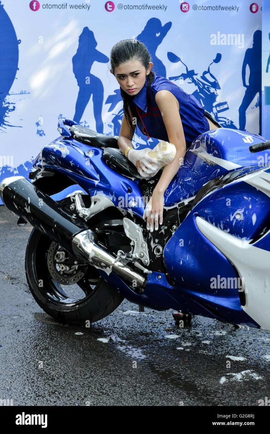 Beautiful woman posing in suzuki motorcycle when photo contest in automotive event tumplek blek 2016, Jakarta, Indonesia Stock Photo