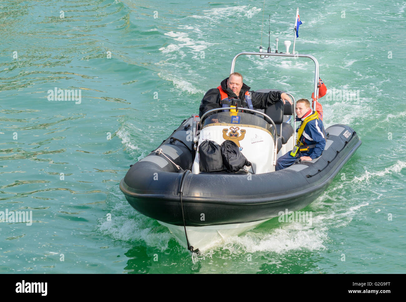 Inflatable rib boat speeding along a river. - Stock Image