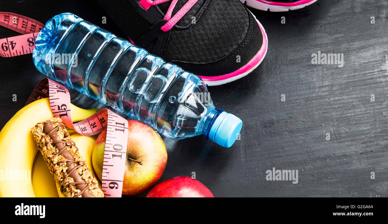 Fruits, water bottle, cereal bar and training shoes, sport itmes, healthy lifestyle - Stock Image