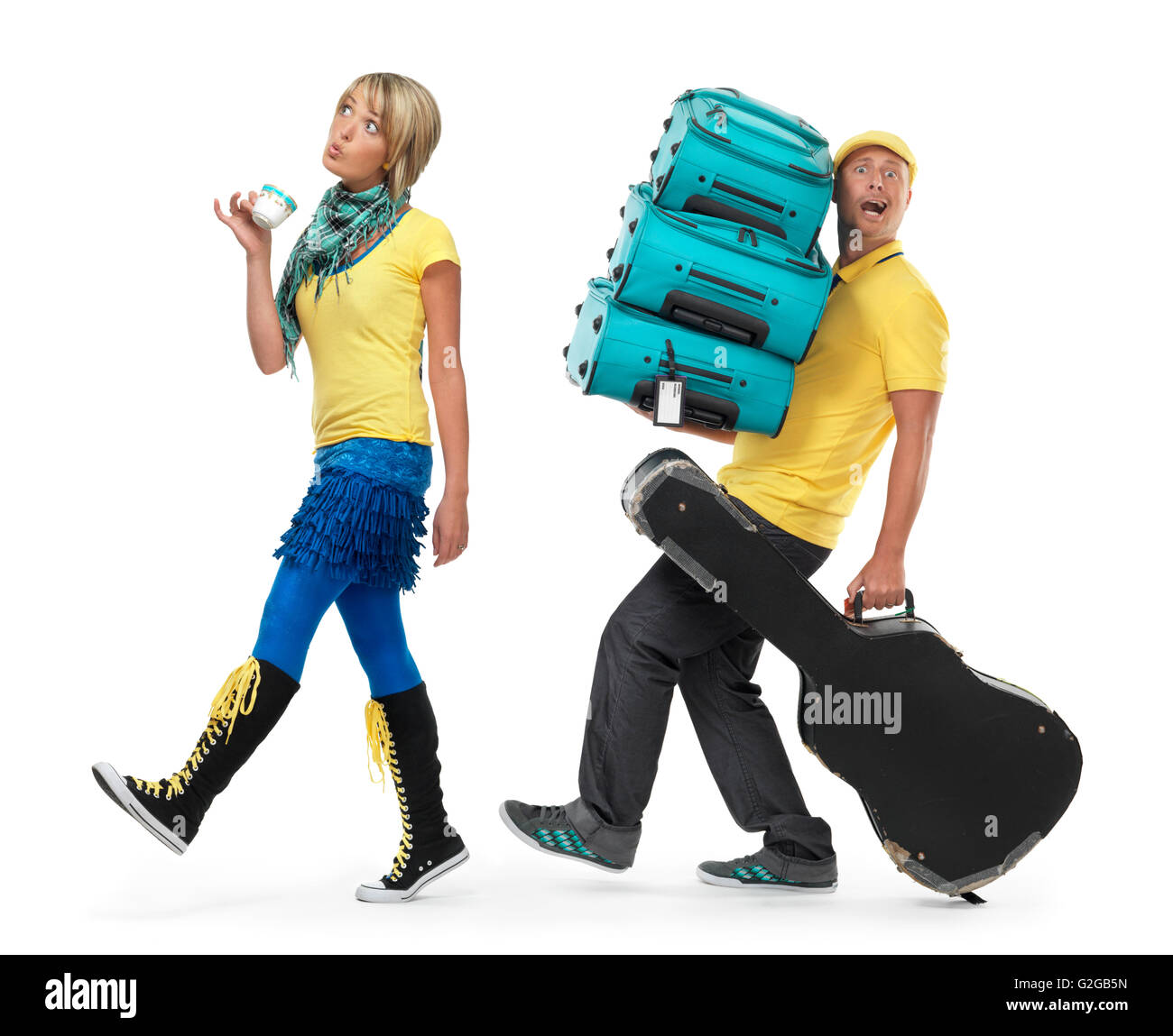 Young couple traveling, woman walking holding a cup of coffee while the man is carrying the luggage - Stock Image