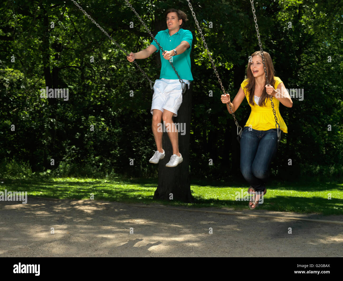Young couple having fun on swings on a playground, Toronto, Ontario Province, Canada - Stock Image
