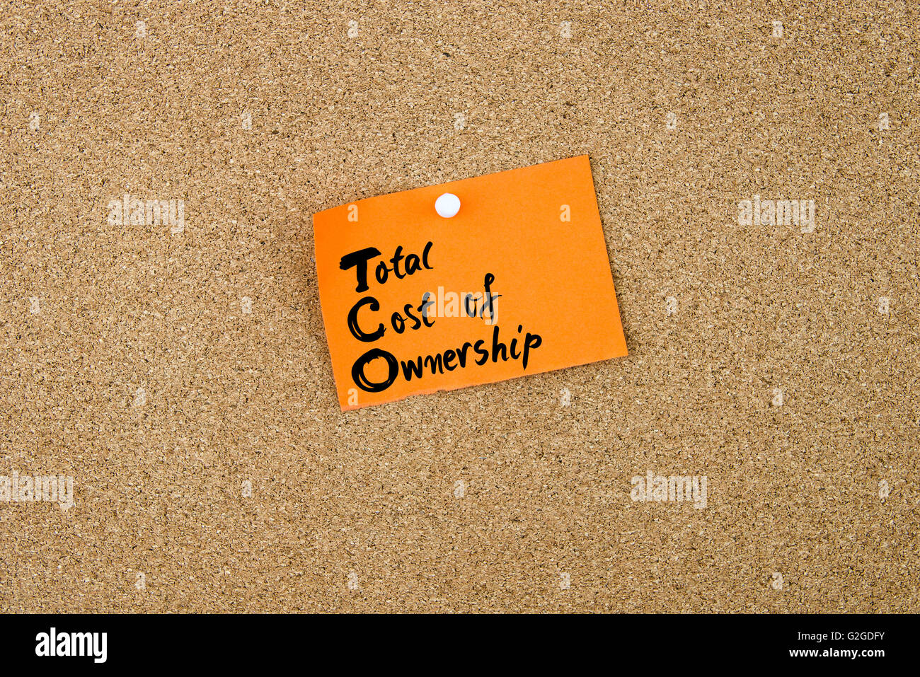 Business Acronym TCO as Total Cost Of Ownership written on orange paper note pinned on cork board with white thumbtacks, - Stock Image