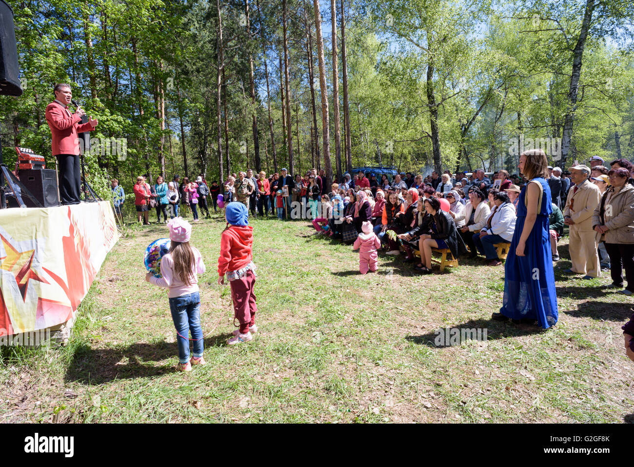 Russian families enjoy a music concert as part of the Victory Day Celebration in a forest on the 9th of May 2016 - Stock Image