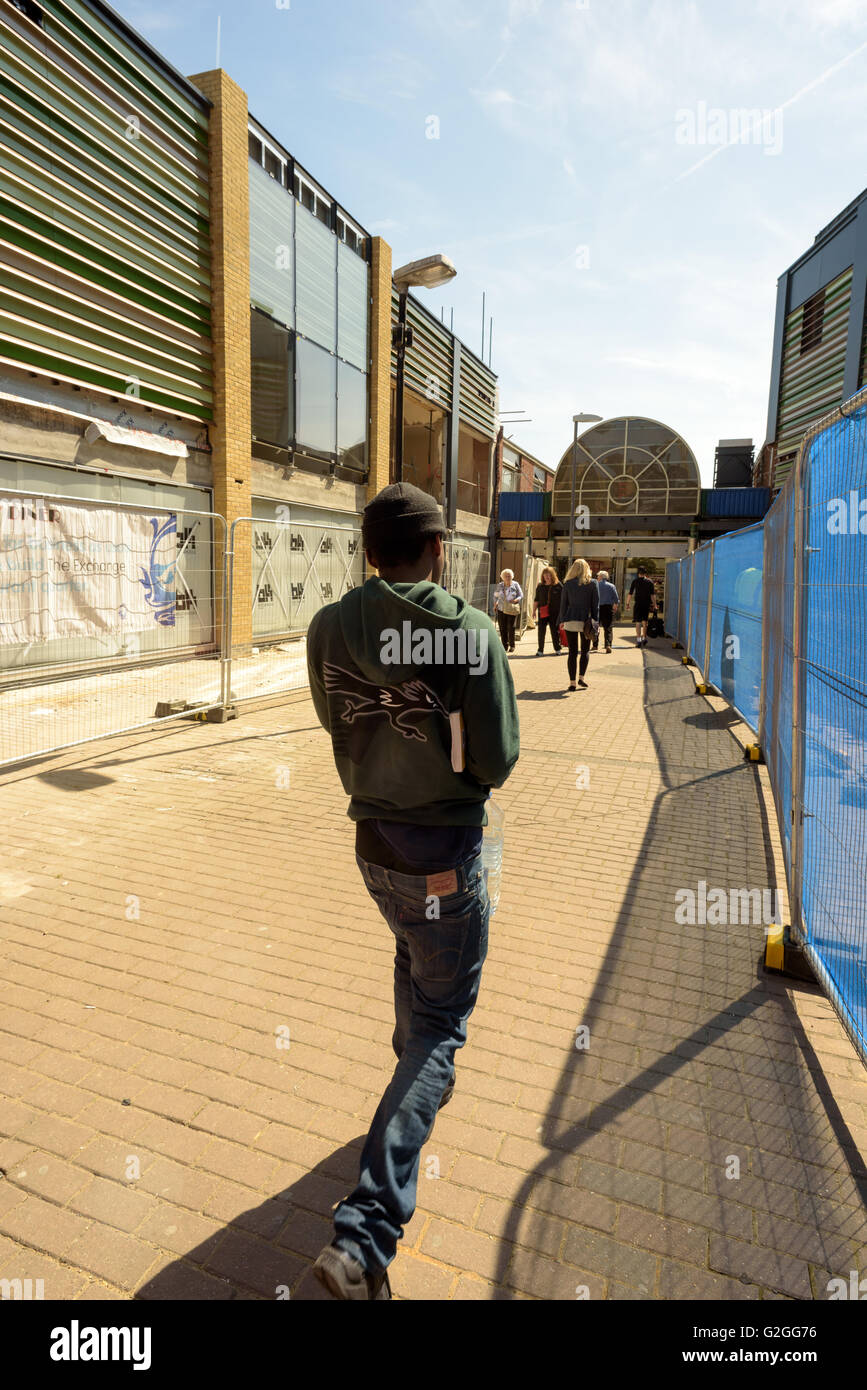 Black youth walking on a high street under renovation in Chelmsford City Essex England in sunshine - Stock Image