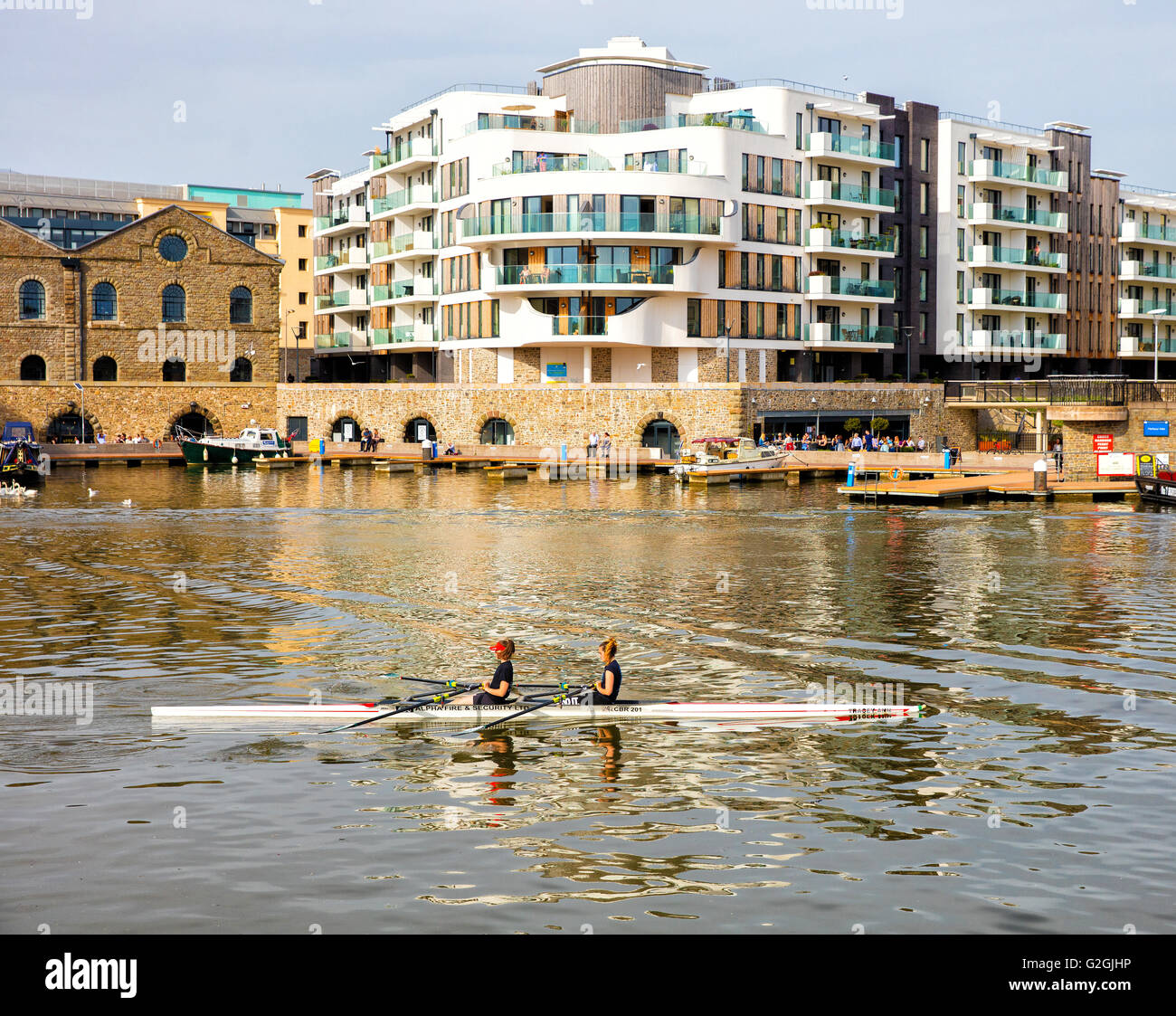 Double scull rowers on Bristol floating harbour near the SS Great Britain - Stock Image