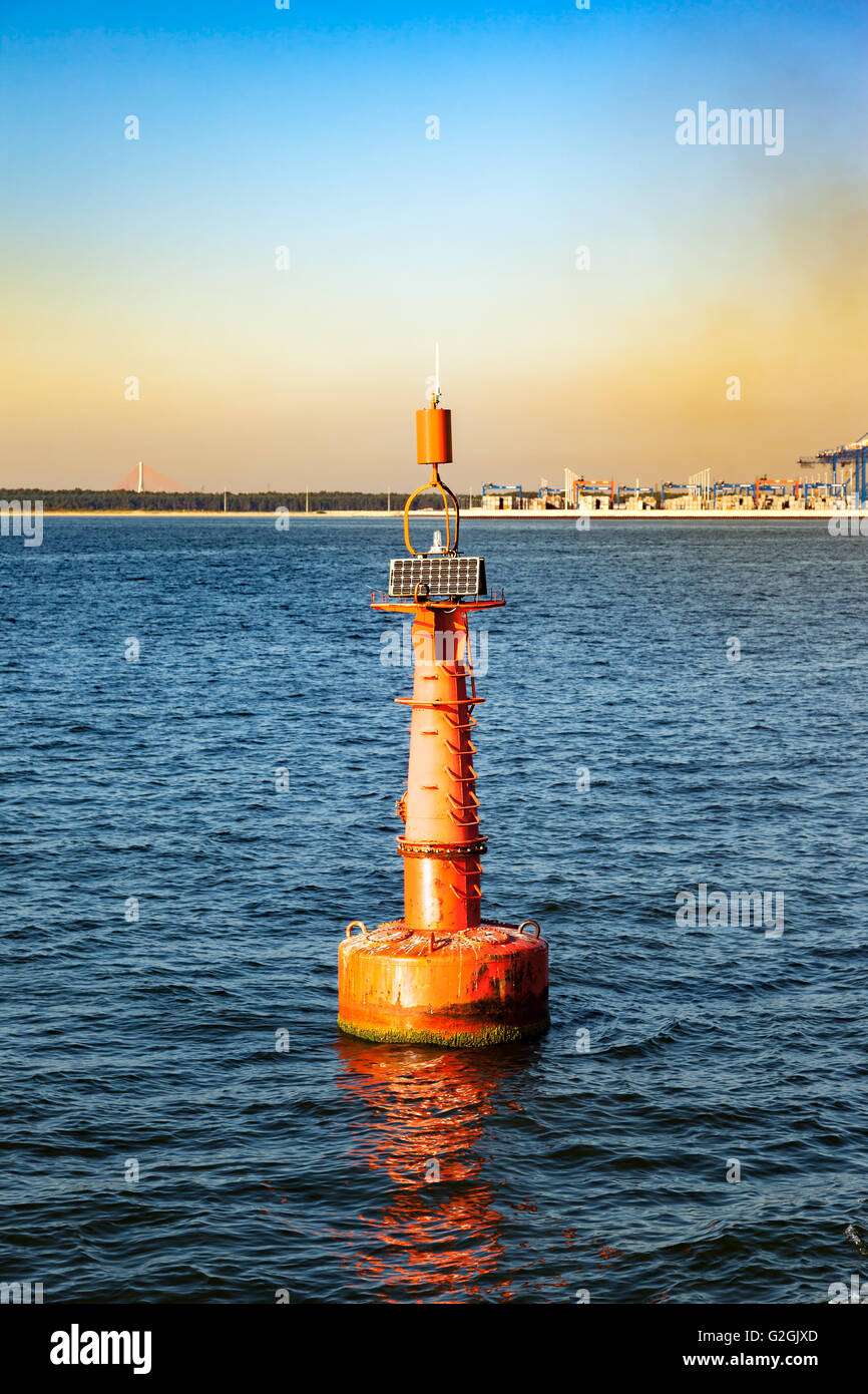 Navigation red buoy at the edge of a fairway. - Stock Image