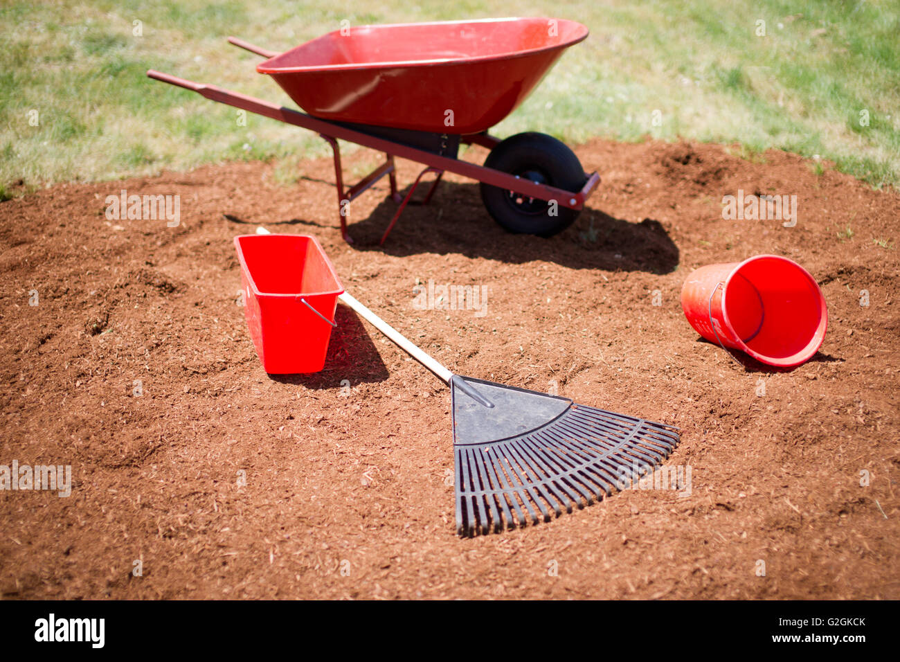 Wheelbarrow, Buckets and Rake on Pile of Mulch - Stock Image