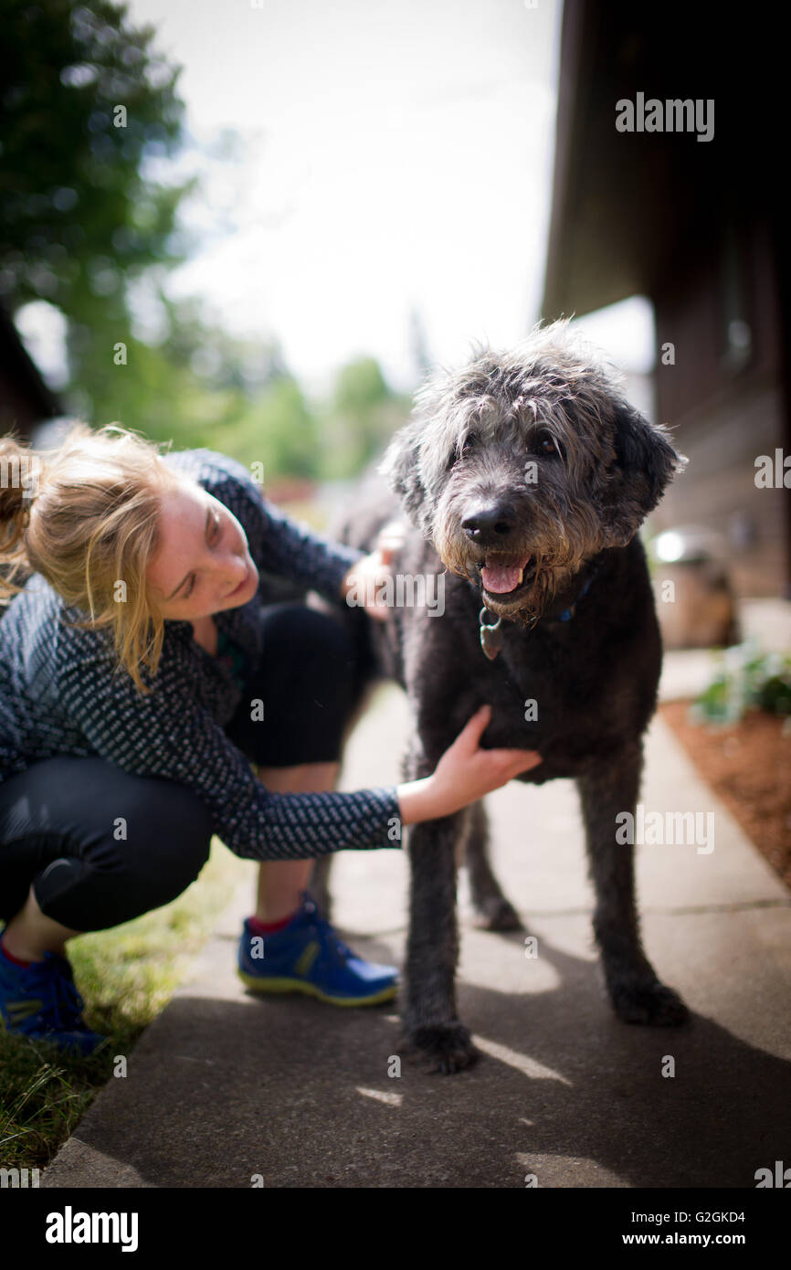 Young Adult Woman with Dog Outside - Stock Image