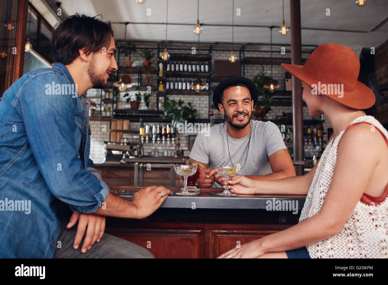 Three young friends smiling and sitting in a cafe having drinks together. Young modern people sitting in the coffee - Stock Image