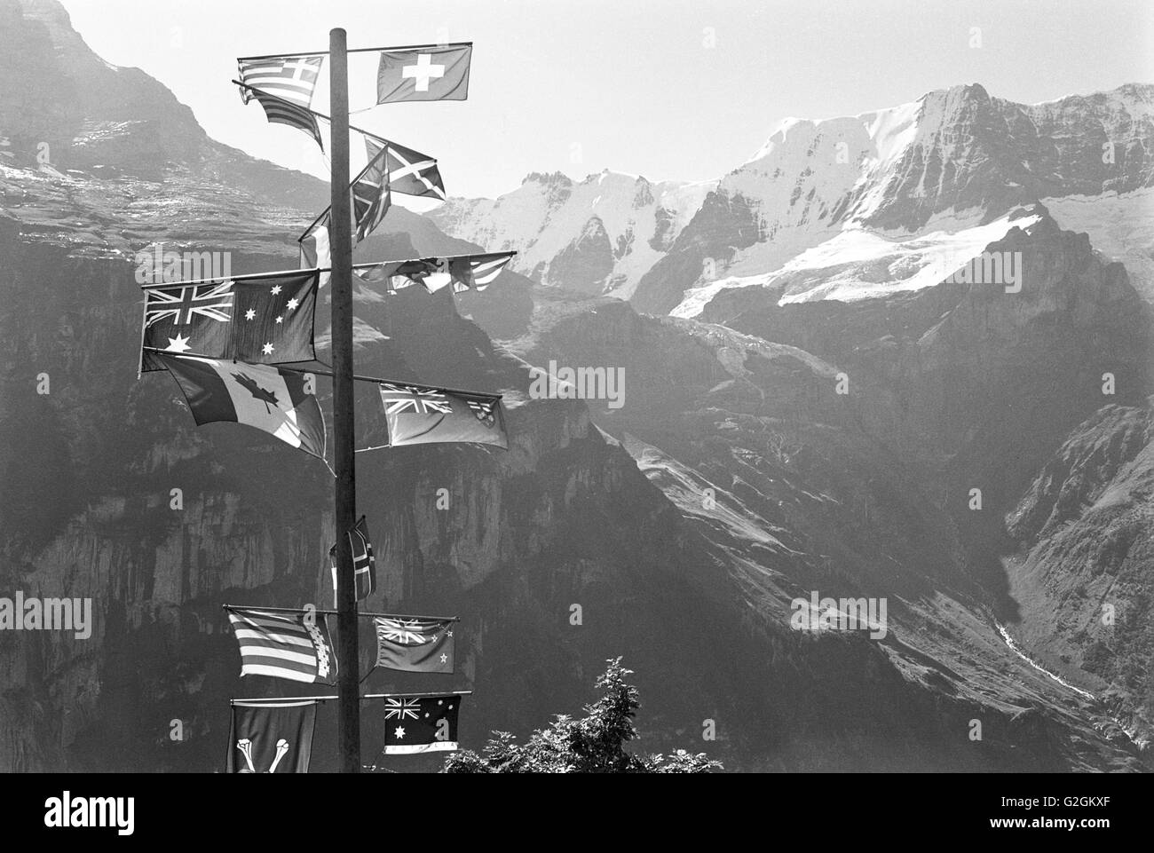 International Flags on Pole With Mountains in Background, Switzerland - Stock Image
