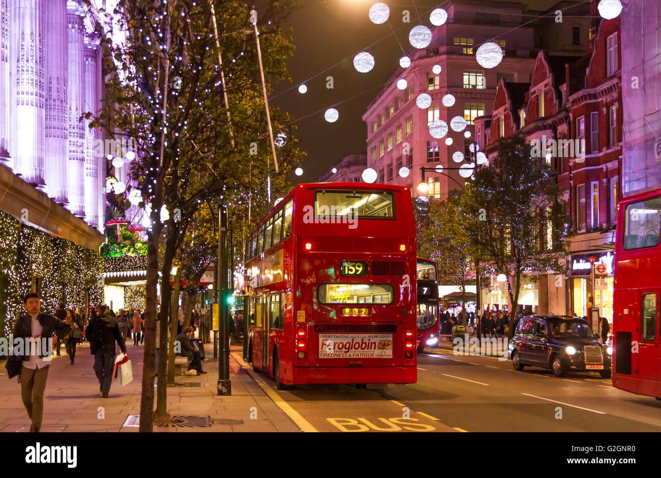 A London bus stops  outside Selfridges Oxford Street at Christmas time ,Oxford St ,London UK - Stock Image