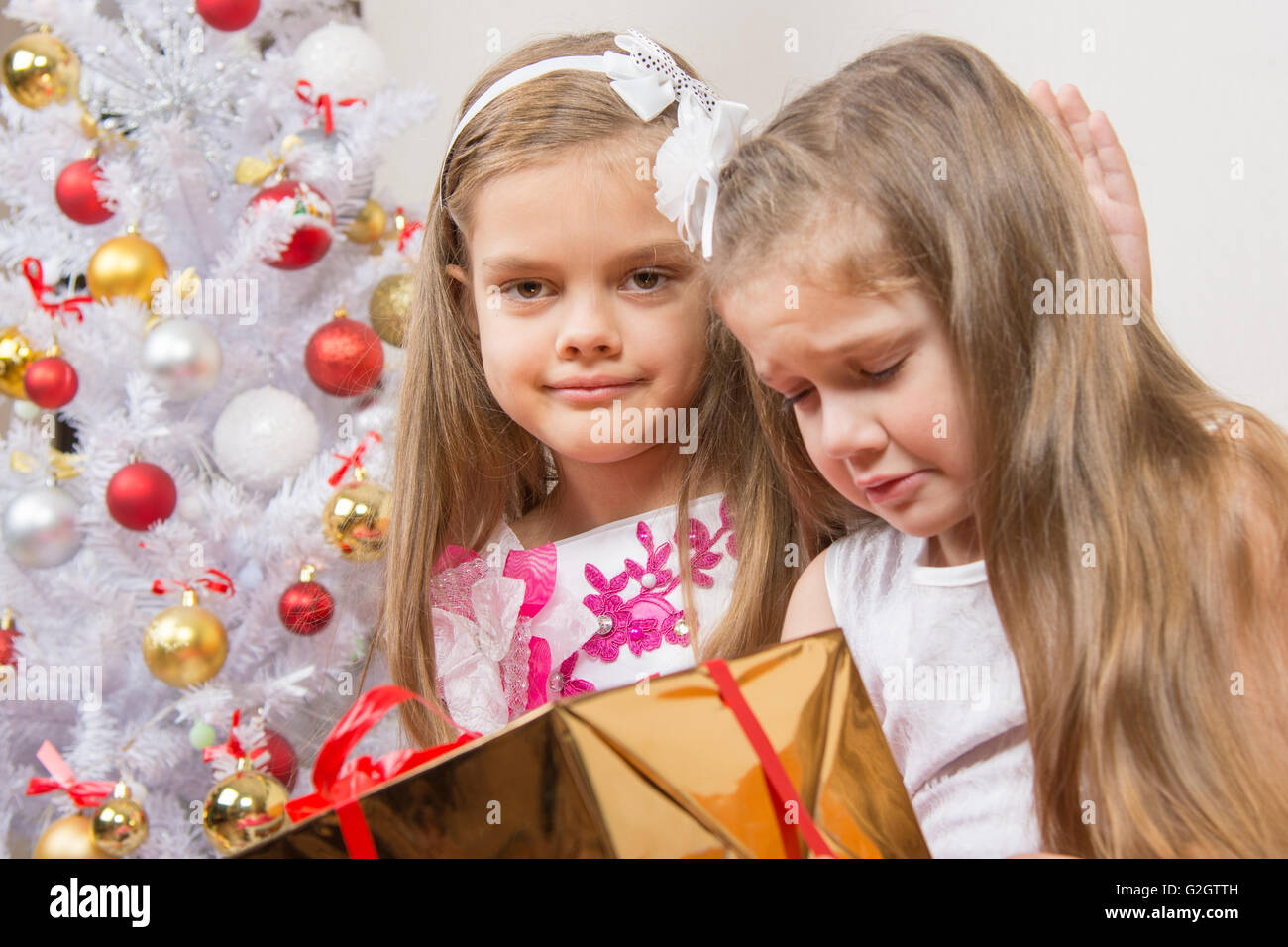The girl gave the wrong gift, another girl comforting her - Stock Image