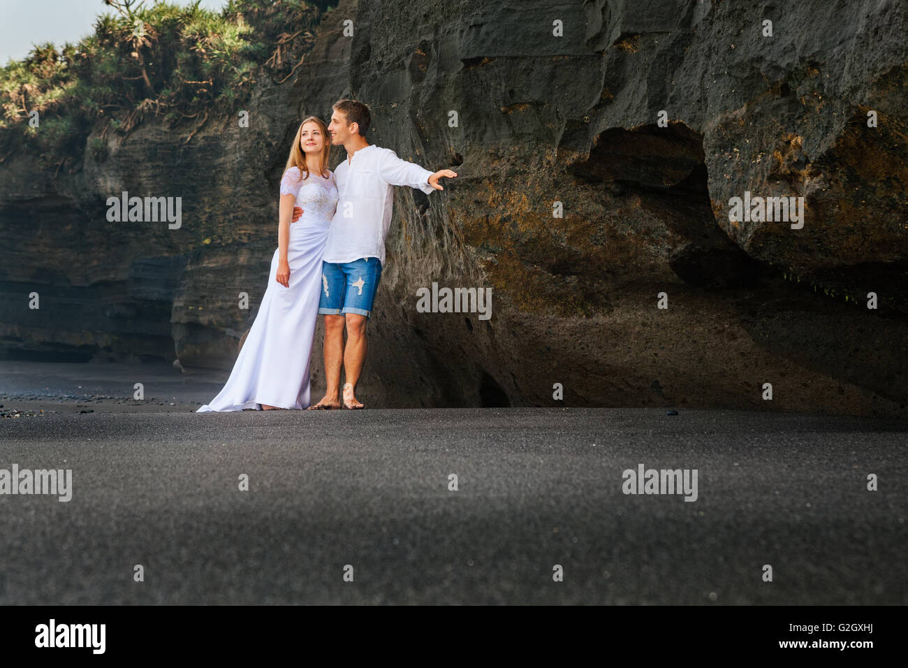 Happy young family on honeymoon holidays - just married loving man and woman embracing  on sand beach with black - Stock Image
