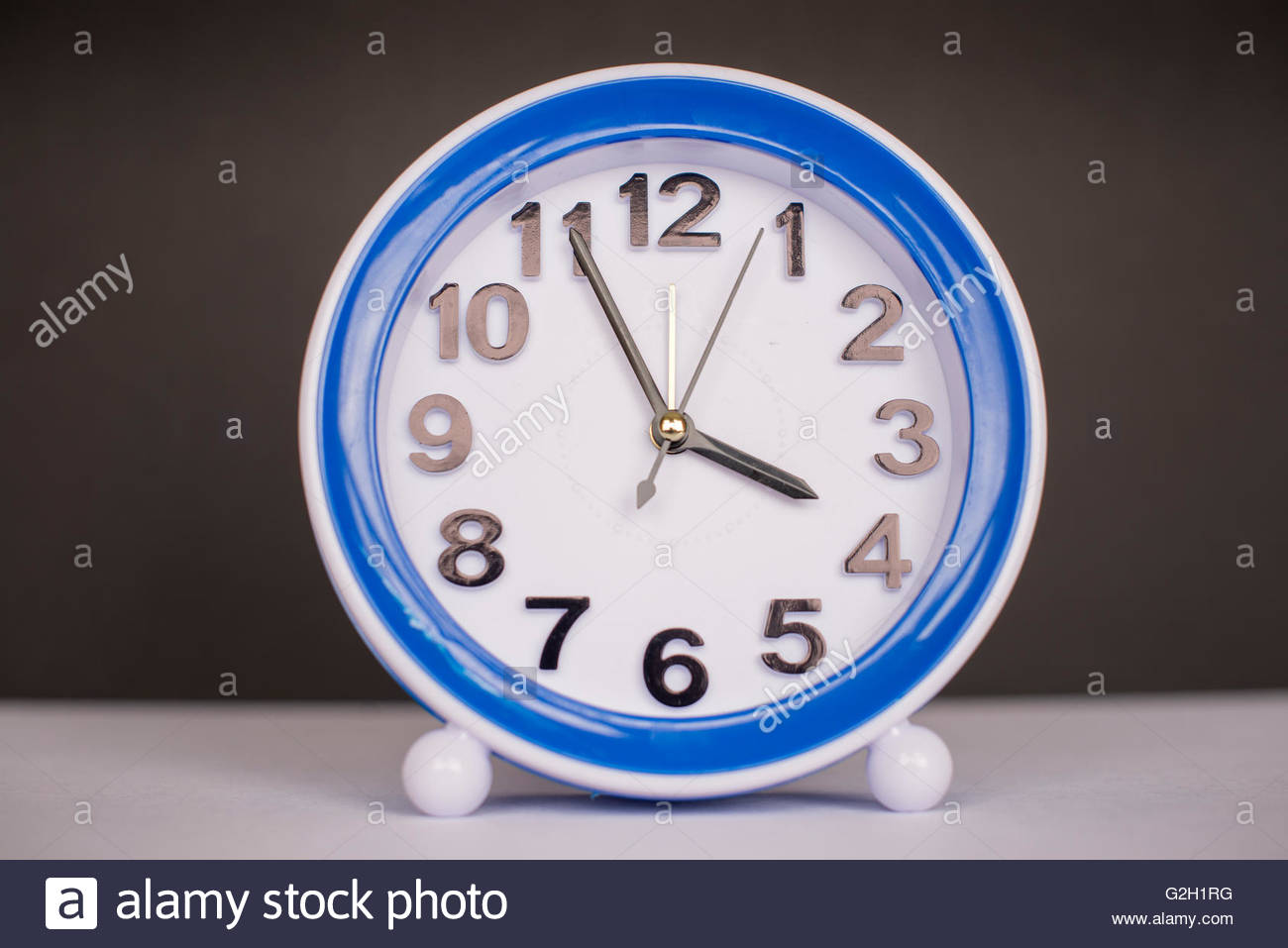 Blue table clock paced on a white surface with a black background. - Stock Image