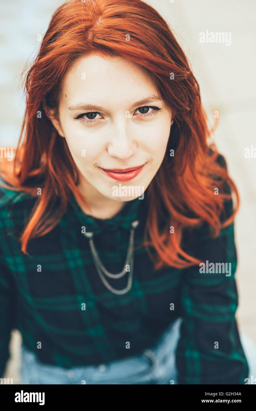 Half length of young handsome caucasian redhead straight hair woman looking in camera smiling, wearing checked blue - Stock Image
