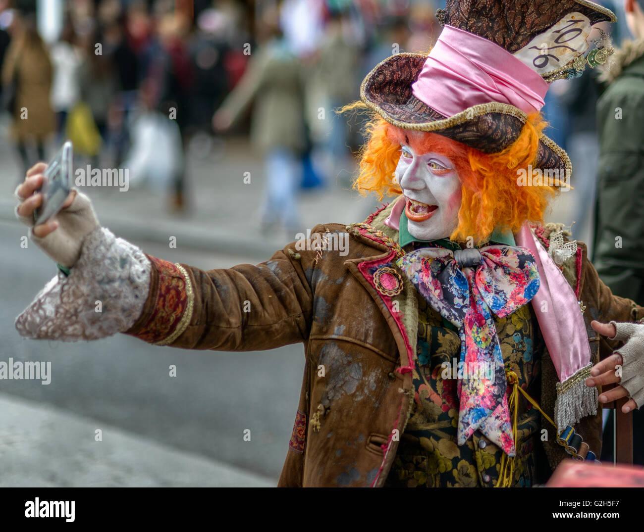 A Mad Hatter impersonator taking a selfie in Camden, near Camden Lock, London, UK - Stock Image