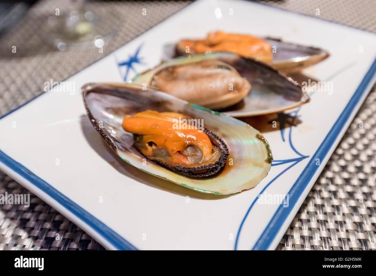Newzealand mussel teppanyaki on white dish - Stock Image