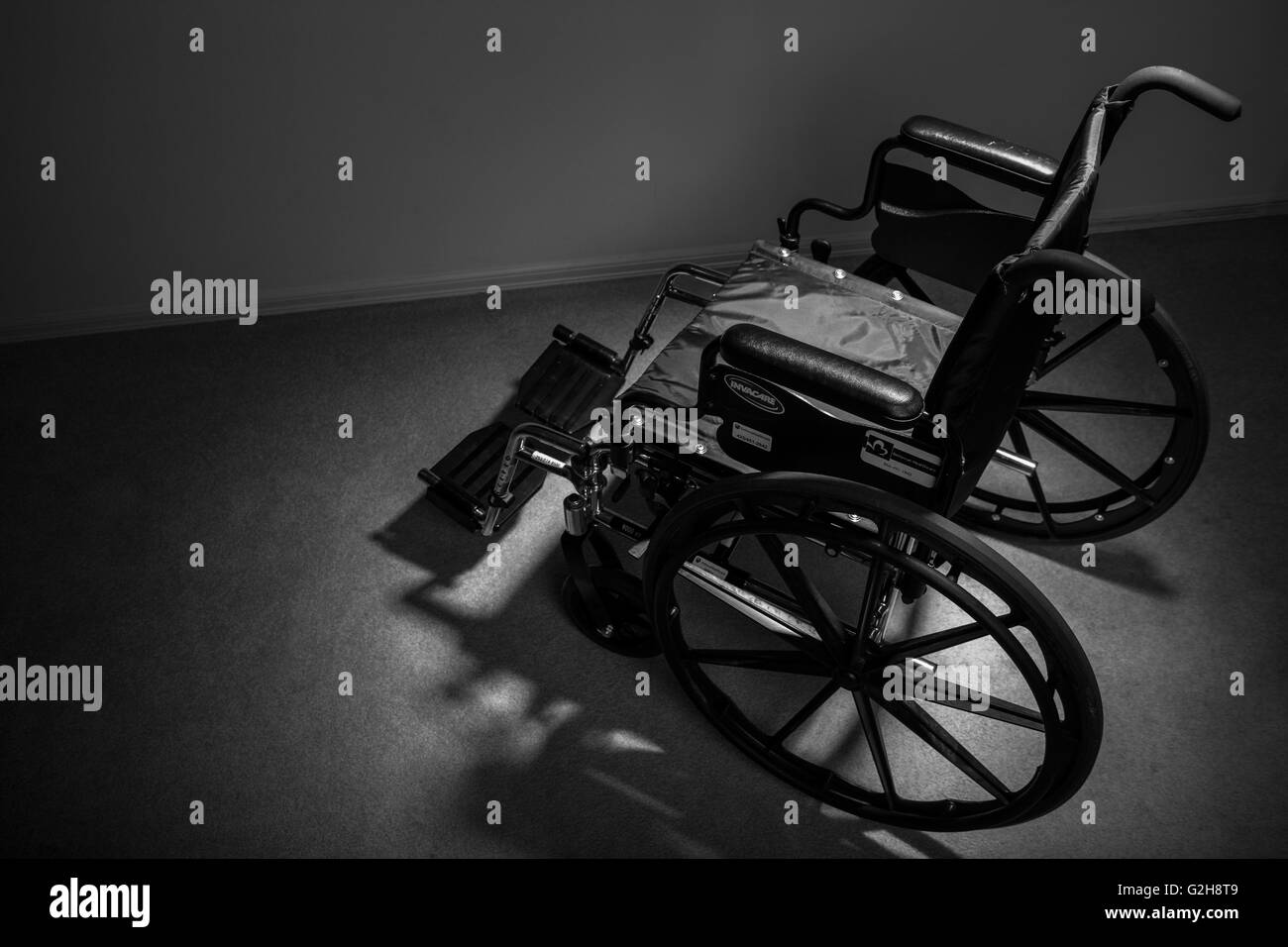 Wheelchair facing away, reinforcing the feeling of isolation and depression that can be associated with personal - Stock Image