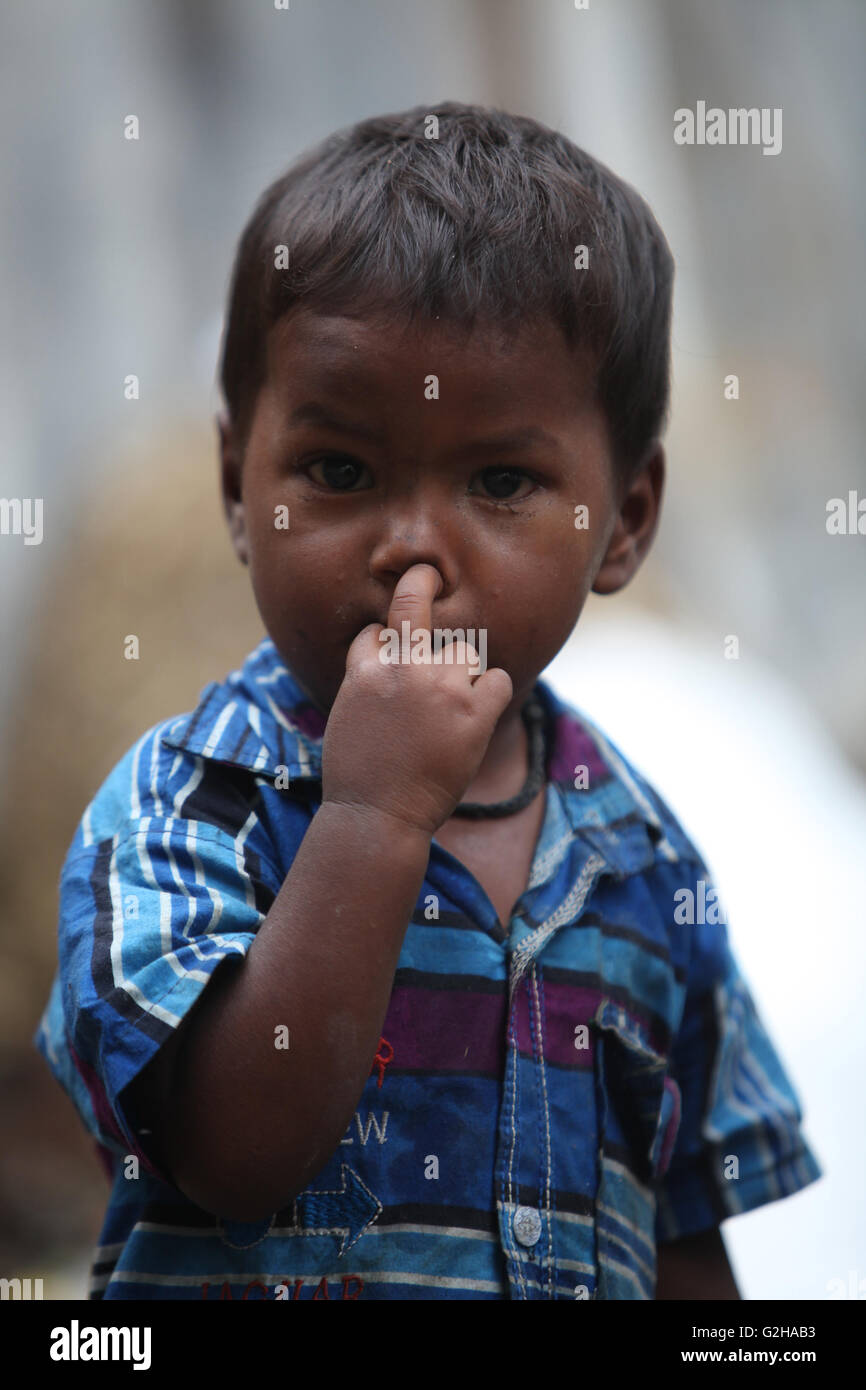 A poor little boy in blue shirt from India picking his nose. - Stock Image