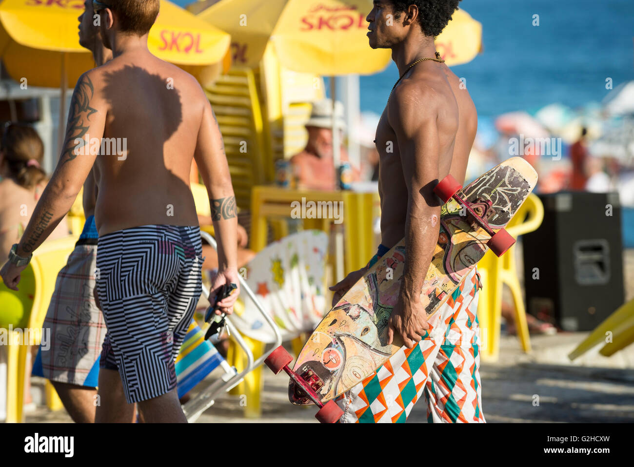 RIO DE JANEIRO - MARCH 6, 2016: Carioca Brazilians walk in front of a yellow kiosk on the beachfront boardwalk at - Stock Image