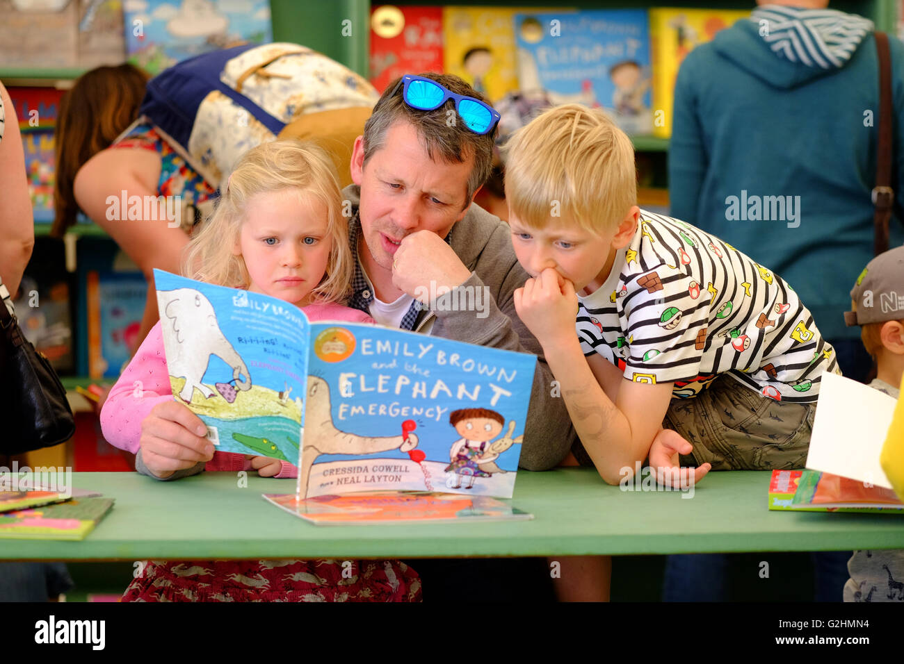 Hay Festival, Wales, UK - May 2016 -  A young family sits and reads together in the Hay Festival bookshop on Day - Stock Image