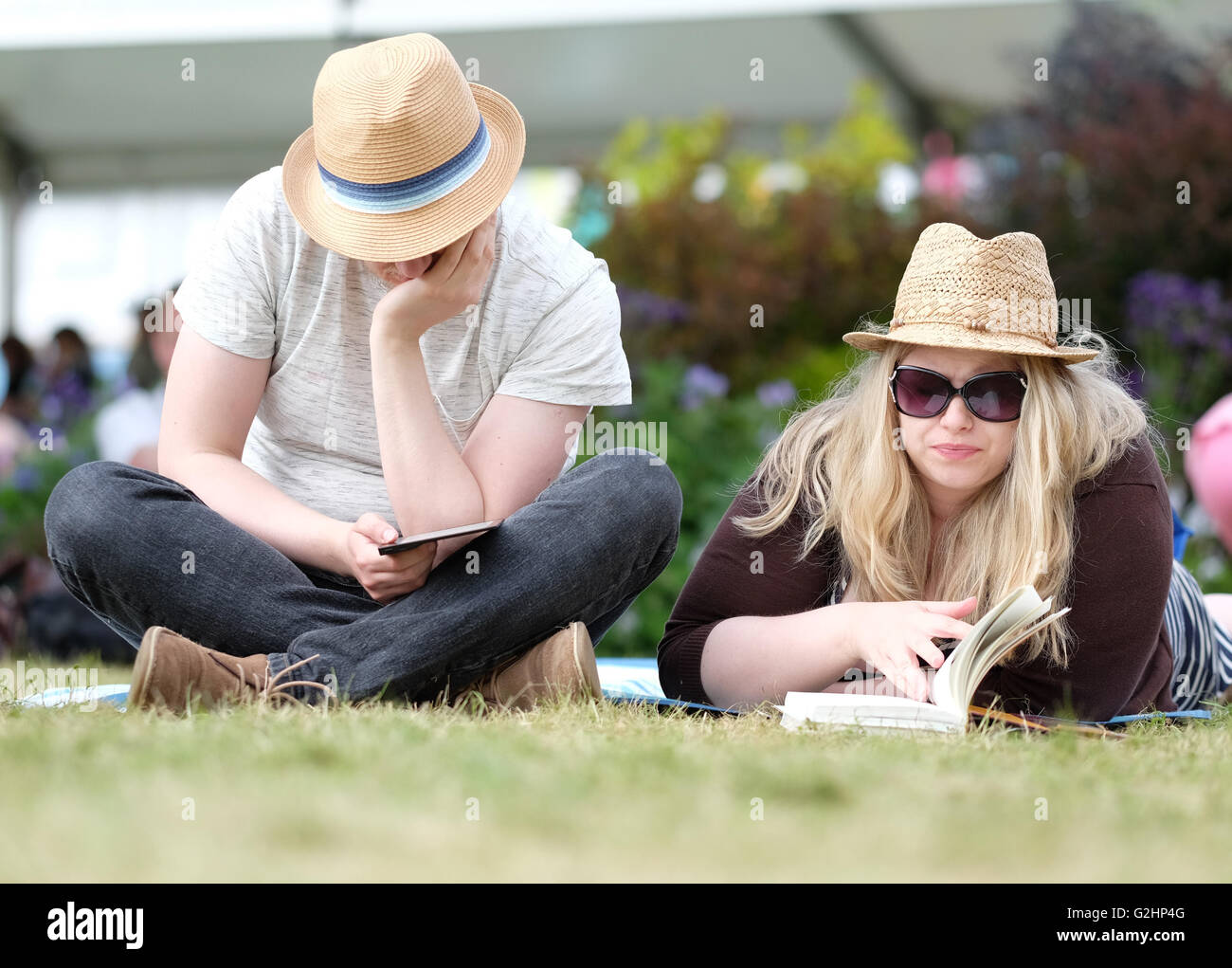Hay Festival, Wales, UK - May 2016 -  A couple relax reading on the Hay Book Festival lawns between events. - Stock Image