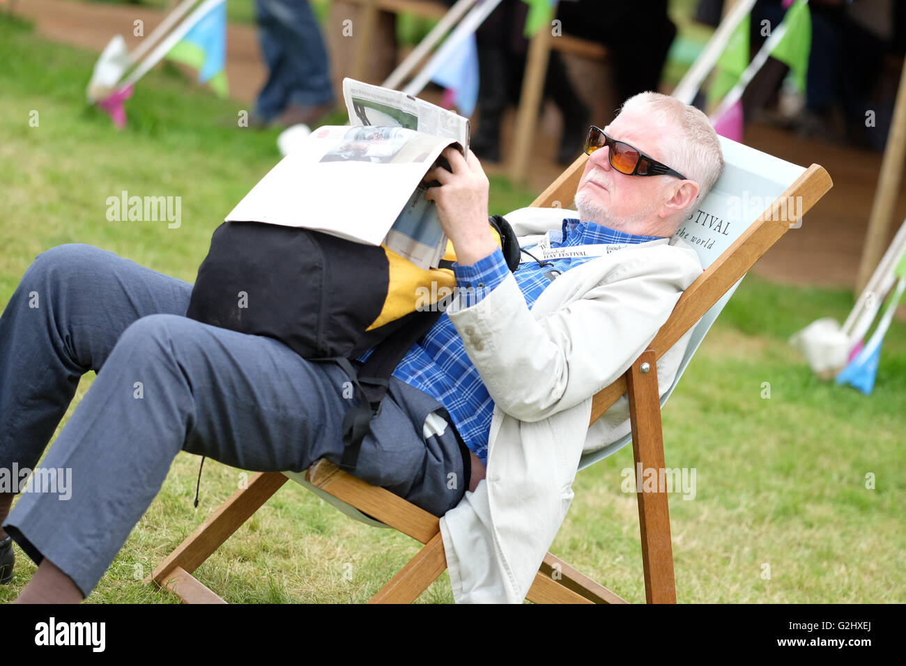 Hay Festival, Wales, UK - June 2016 -  A visitor finds time to sit and read his newspaper on the Hay Book Festival - Stock Image