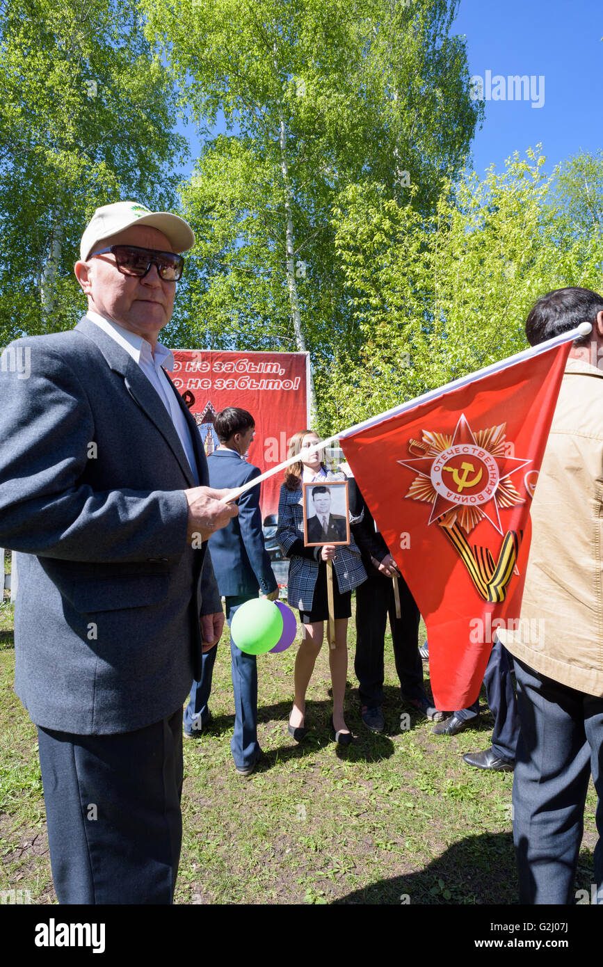 People remember Victory Day in Russian on the 9th of May 2016, holding flowers and placards with soldiers who fought - Stock Image