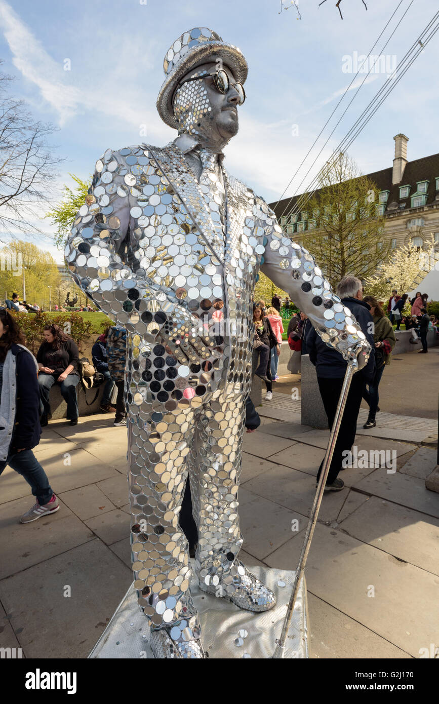 Silver painted statue artist entertaining tourists on the banks of the River Thames in London - Stock Image