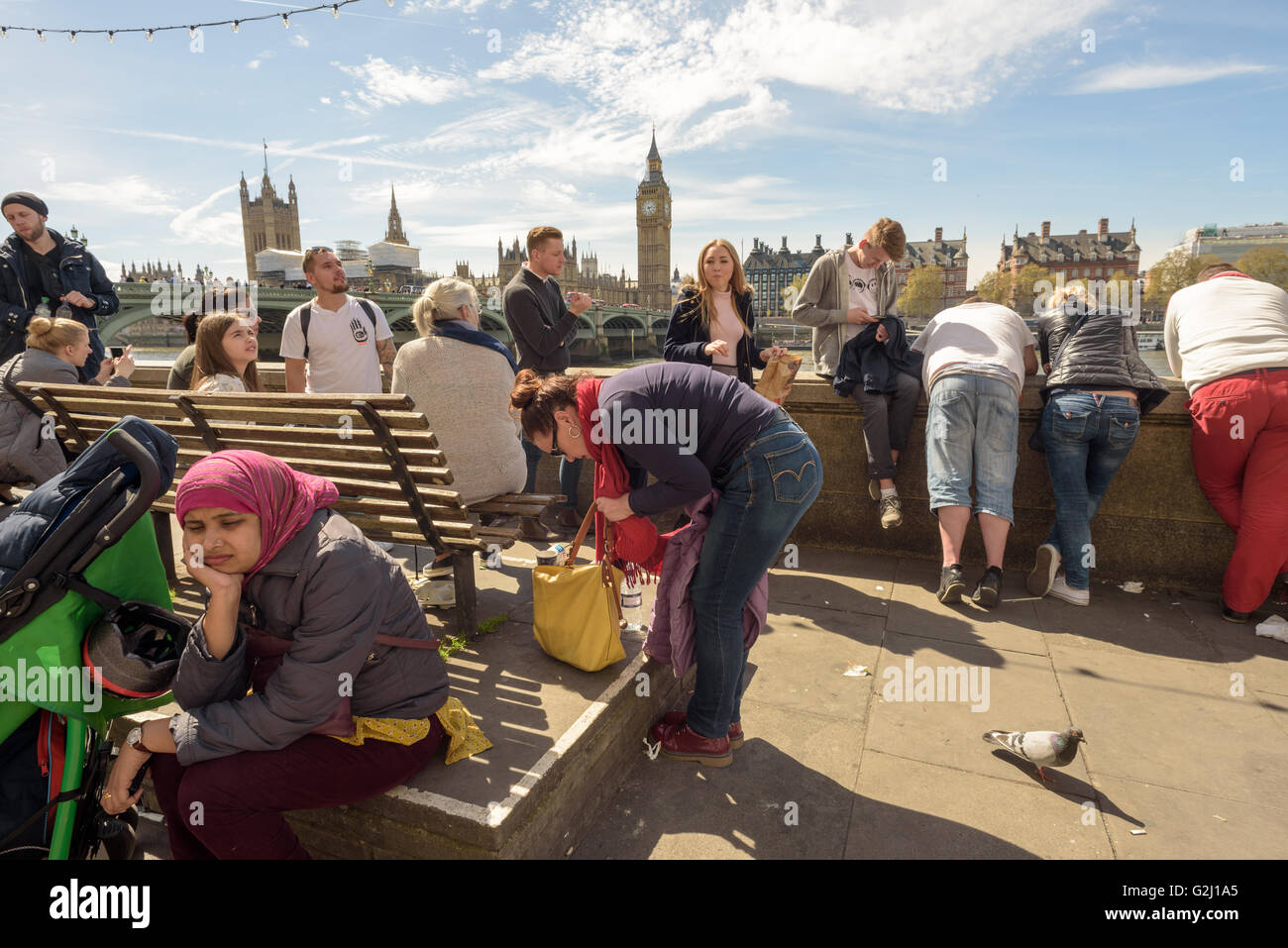 Tourists relaxing on the Queen's Walk with Big Ben and the Houses of Parliament in the Background - Stock Image
