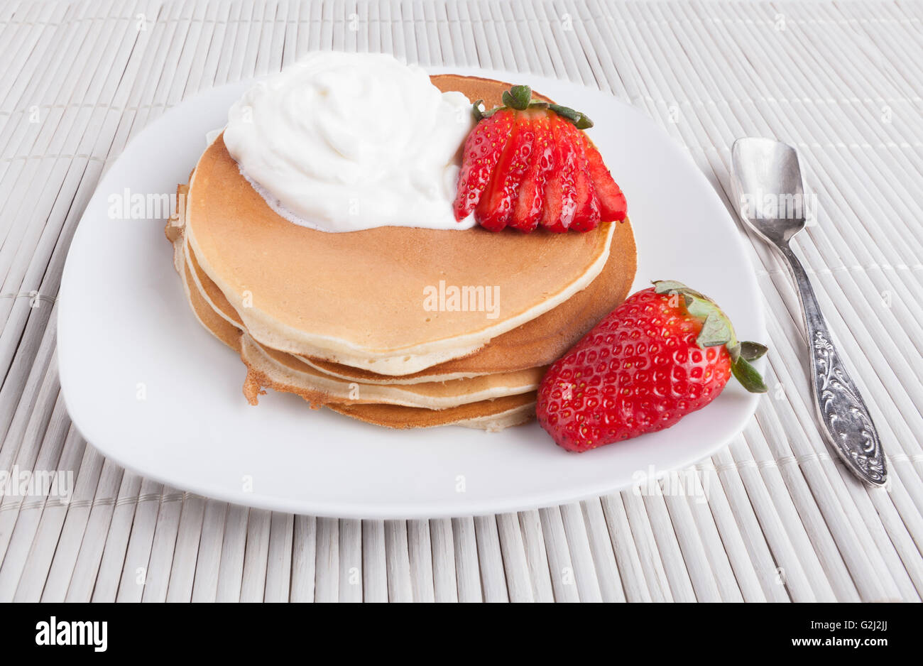 Pancakes on white background with cream  strawberry and silver spoon Stock Photo