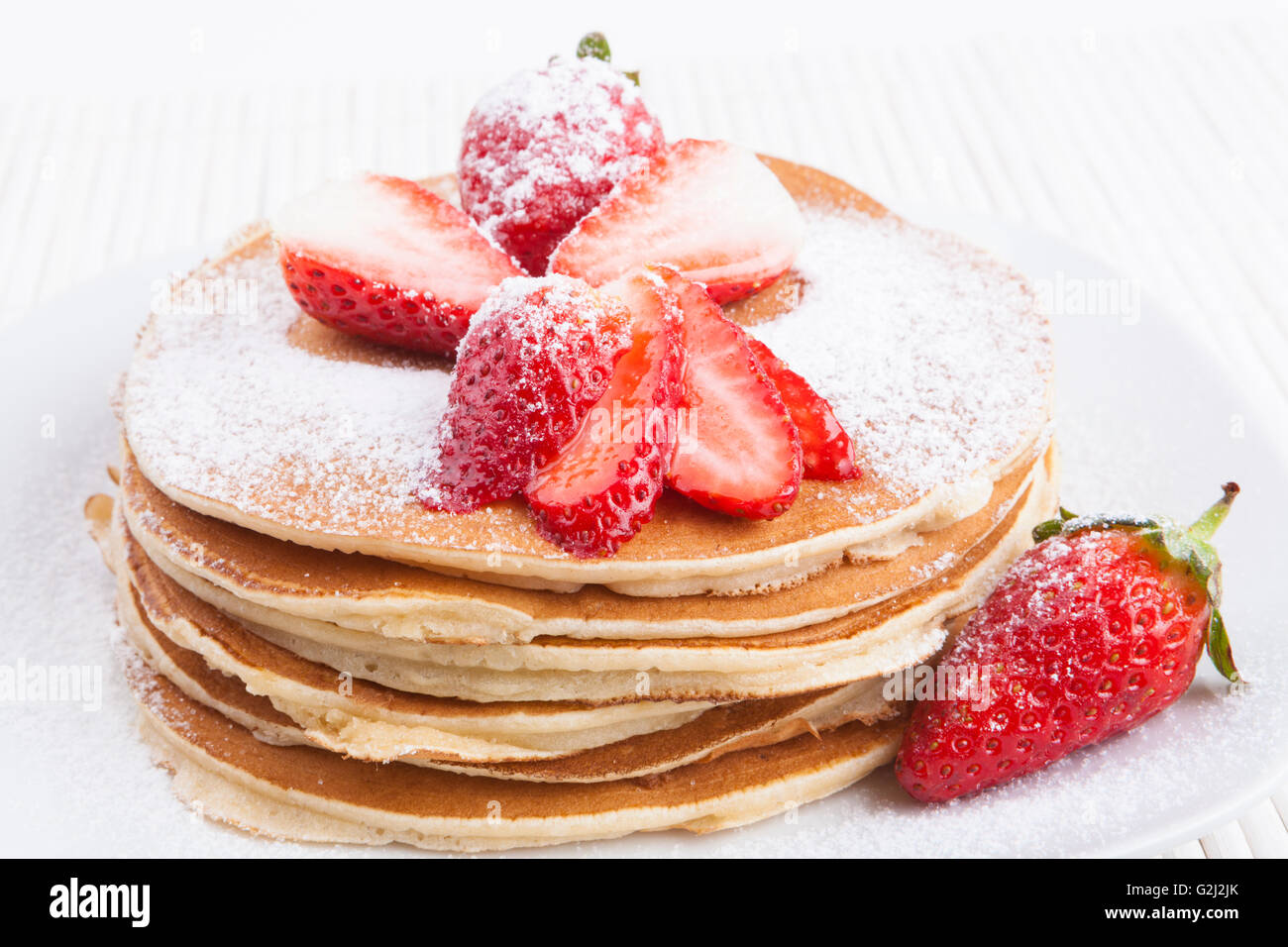 Pancakes on white background with  strawberry and sugar - Stock Image
