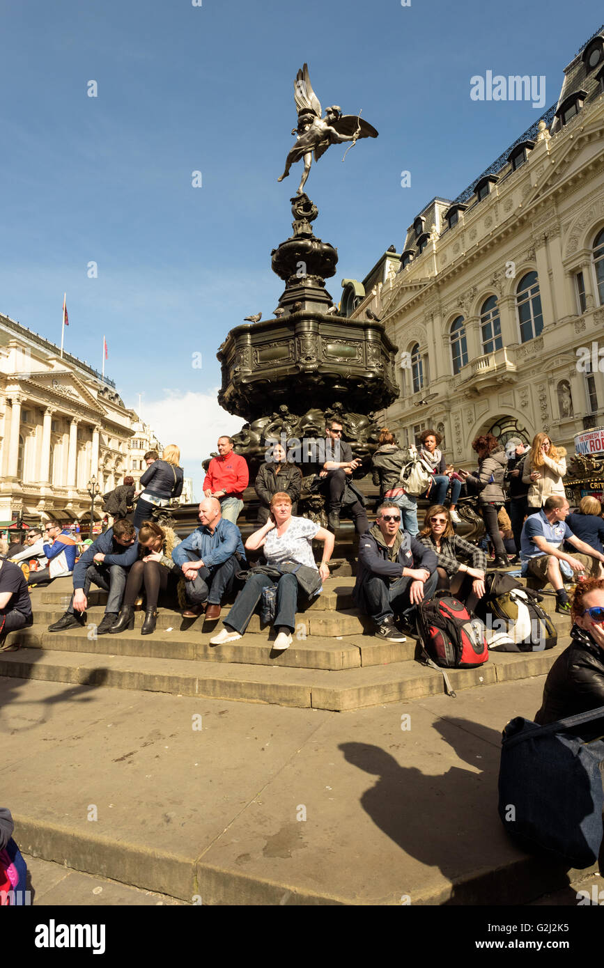 People sitting on the Shaftesbury Memorial Fountain with the Greek god Anteros or Eros in London, Piccadilly Circus - Stock Image
